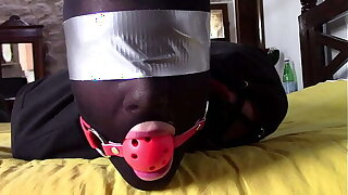 Laura Hardcore is wearing panthyhose and high heels. She's hogtied, masked, blindfolded and ballgagged